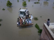 A bulldozer carries flood victims to a near by rooftop in Muzaffargarh district of Pakistan's Punjab province