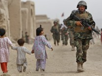 Afghan Army and Canadian soldiers conduct patrol in the village of Bazaar e Panjwaii