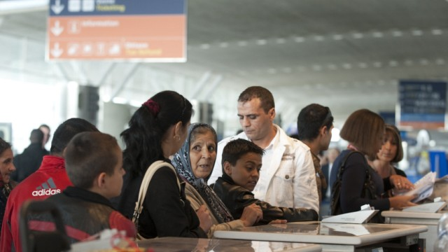 Roma who are part of a voluntary repatriation scheme stand at the check-in desk for their flight to Romania at the Charles-de-Gaulle airport
