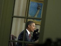 U.S. President Barack Obama is seen in the Oval Office through a window as he addresses the nation about the end of the U.S. combat mission in Iraq at the White House in Washington