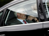German central bank executive Thilo Sarrazin sits in a car leaving the headquarters of the German central bank (Bundesbank) in Frankfurt
