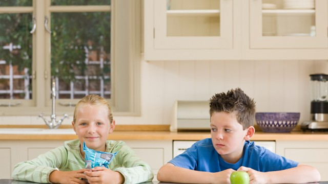 Girl and boy with crisps and apple