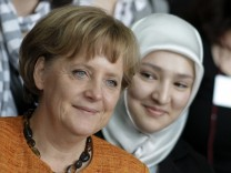 German Chancellor Merkel poses with participants of the youth integration summit in Berlin