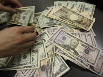 U.S. dollar bills are pictured during a photo opportunity at an office of Interbank Inc. money exchange in Tokyo