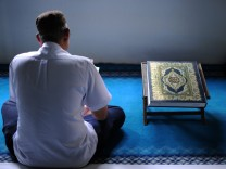 Ein gläubiger Muslim neben einer Prachtausgabe des Koran. Das Foto entstand in  Malaysia.
