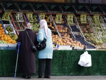 Women wearing headscarves look at shop selling fruits at a street in Berlin's Neukoelln district