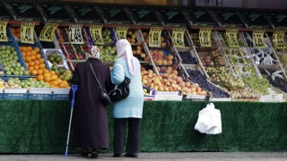 Women wearing headscarves look at shop selling fruits at a street in Berlin's Neukoelln district