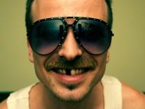 Mann mit Schnurrbart, Sonnenbrille und Zahnlücke