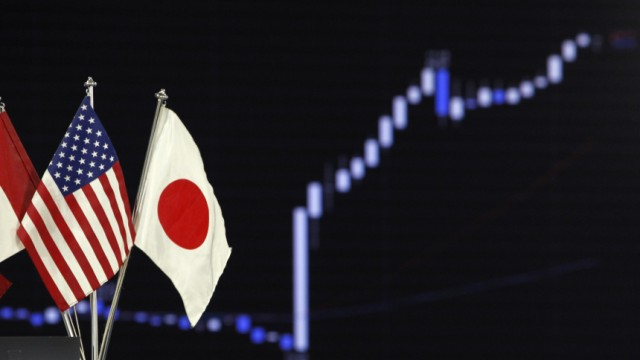 National flags of Japan and the U.S. are seen near a graph displaying the movements of the U.S. dollar and the Japanese yen foreign exchange rates in Tokyo